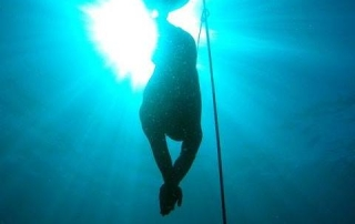 Carl Atkinson freediving down a line with monofin
