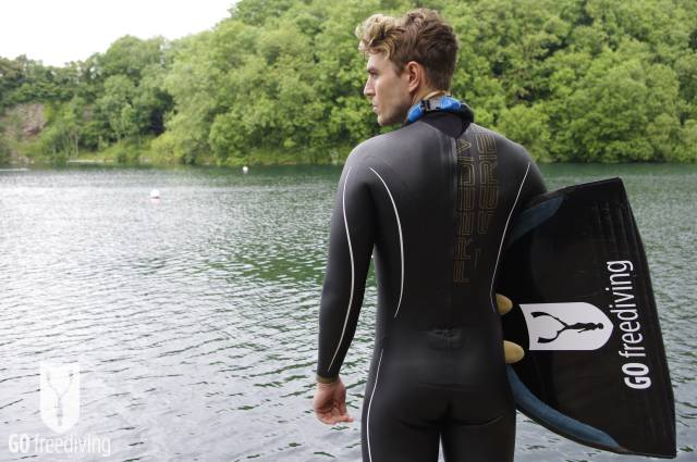 Carl Atkinson wearing Aqua Lung Sport Apnea Freediving suit at Vobster Quay with Go Freediving monofin and neck weight, from behind mid shot 1