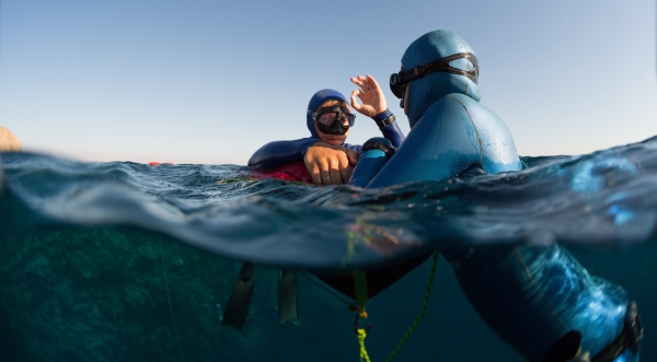 Beginners Guide to Freediving - safety for freediving - Split shot of two free divers training in sea with buoy