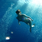 Emma Farrell in a bikini freediving through scuba diver bubbles in Kalymnos, Greece