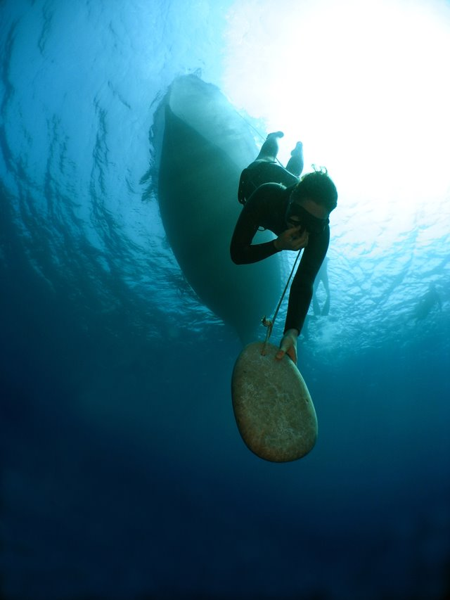 Emma Farrell freediving with a skandalopetra stone in Kalymnos, Greece